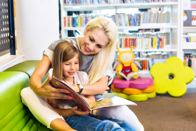 Mother with little girl happily reading book together.